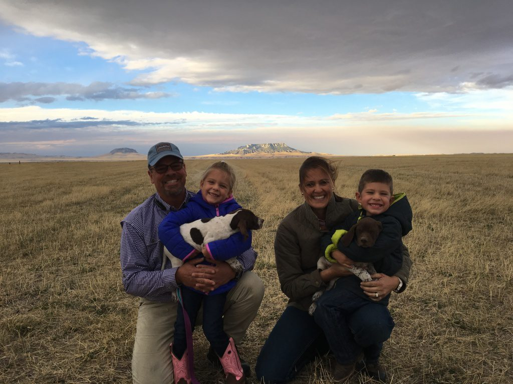 happy customers squatting on a field with their children who are holding two brown-white puppies